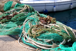 64737032-old-ropes-and-fishing-nets-and-rusty-anchors-on-the-shore-selective-focus